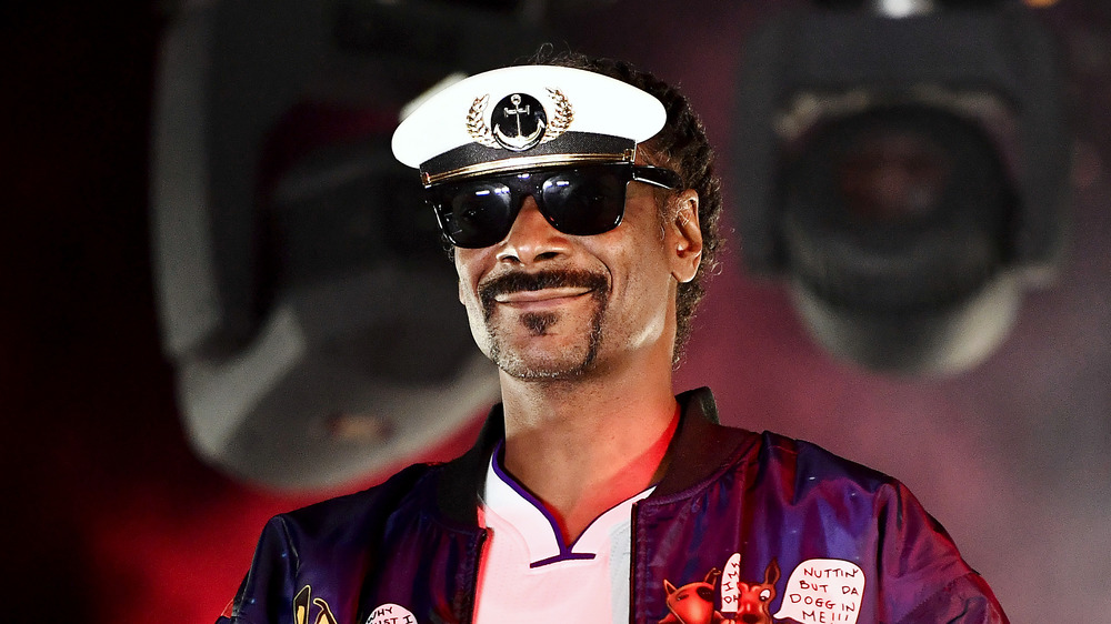 Snoop Dogg smiling onstage wearing aviator sunglasses and a visor