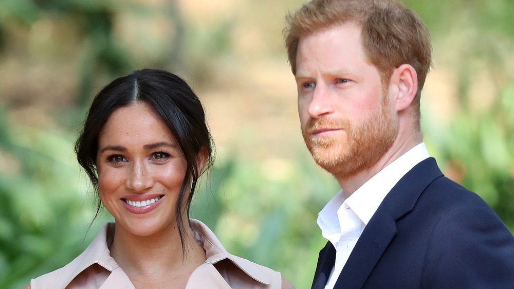 Meghan Markle and Prince Harry looking toward cameras