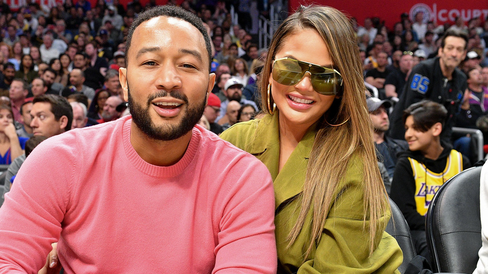 John Legend and Chrissy Teigen at a basketball game