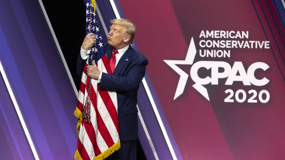 Donald Trump hugs and kisses the American flag during the Conservative Political Action Conference in National Harbor Maryland U.S. on Saturday Feb. 29 2020