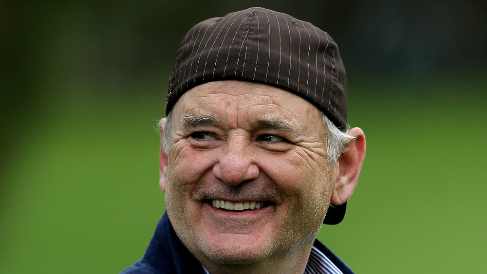 Bill Murray wearing a cap backwards as he grins at something