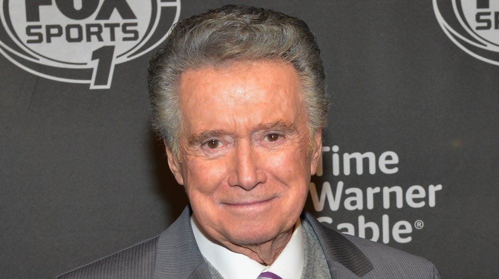Regis Philbin in a grey suit, looking straight at the camera with a small smile