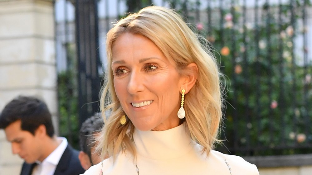 Céline Dion in a white dress and gold earrings, smiling and looking off to the side while walking outdoors