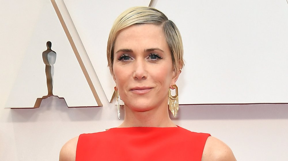 Kristen Wiig in a red dress, smirking on the Oscars red carpet
