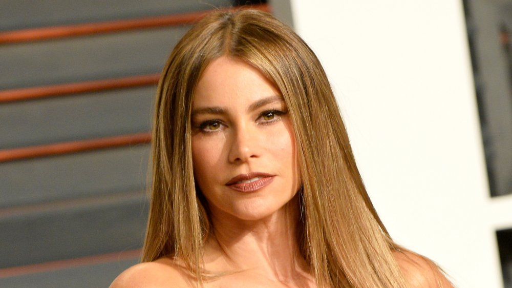 Sofia Vergara in a blue dress, posing with a neutral expression on the red carpet