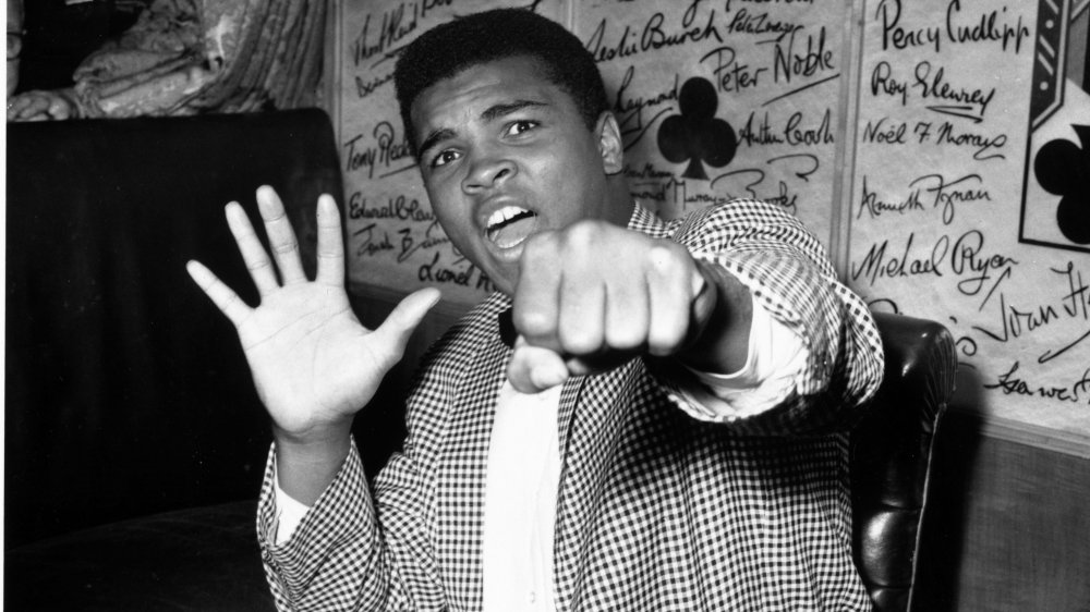 Black-and-white photo of Muhammad Ali in street clothes, striking a playful boxing pose