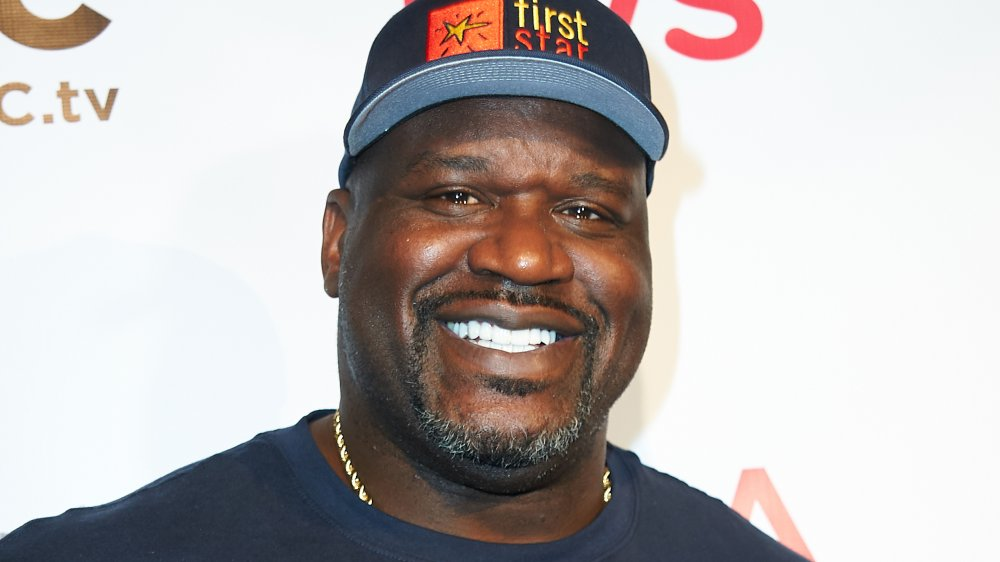 Shaquille O'Neal smiling in a blue t-shirt and hat