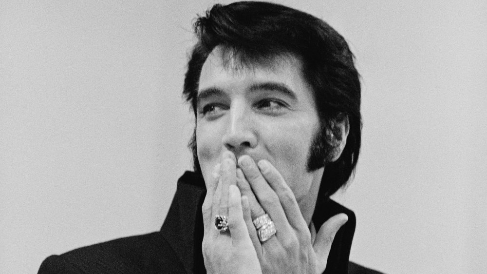 A black and white photo of Elvis Presley wearing rings and with sideburns covering his mouth with his hands