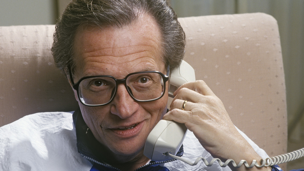 Larry King holding a phone while wearing black rimmed glasses
