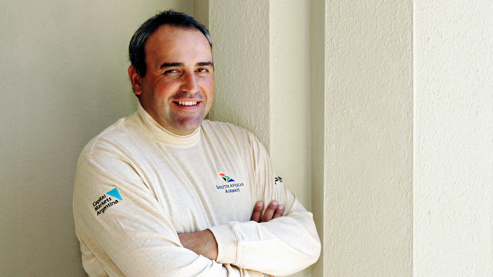 Angel Cabrera posing with arms crossed up against a wall