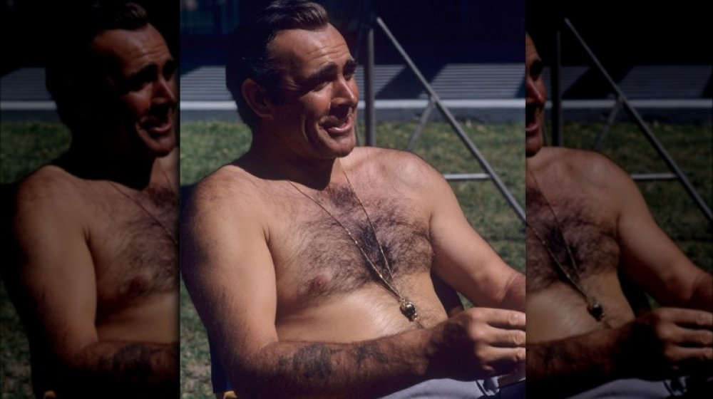 Sean Connery shows off his tattoos while relaxing on the set of Diamonds are Forever in 1971