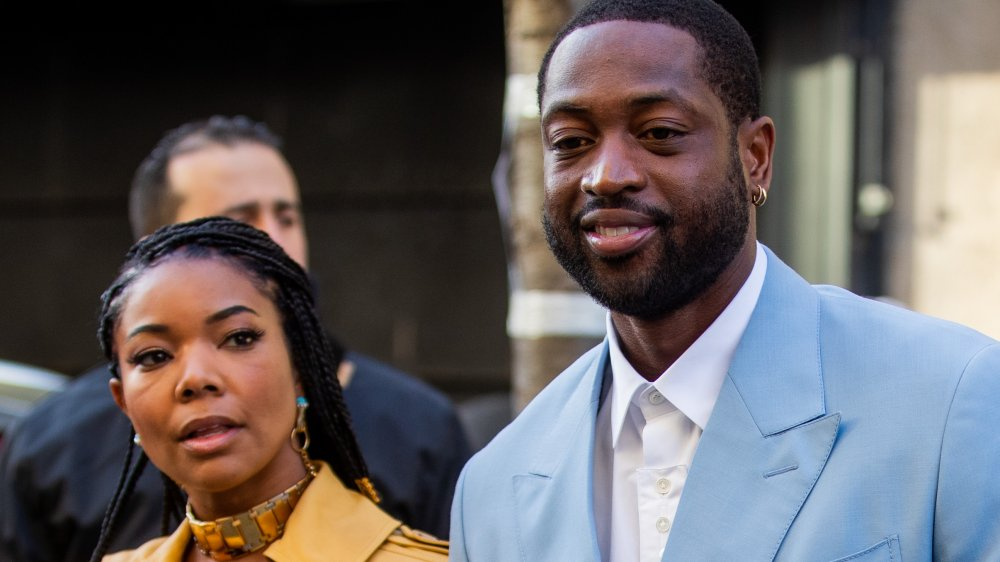 Gabrielle Union in a yellow trench coat, Dwyane Wade in a light blue suit