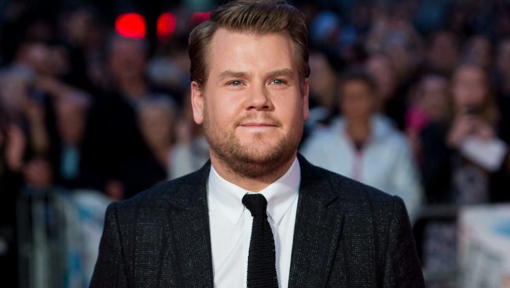 James Corden wearing a black suit and tie on the red carpet