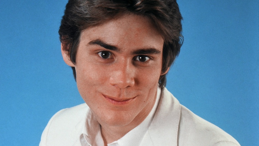 A young Jim Carrey smirking in a portrait session