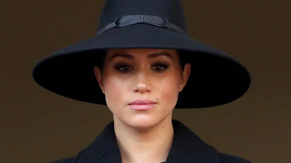 Meghan Markle, the Duchess of Sussex, wearing a hat, looking serious
