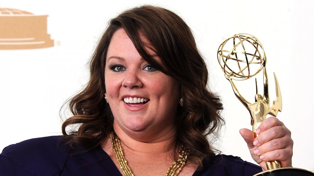 Melissa McCarthy smiling while holding her Emmy Award in 2011