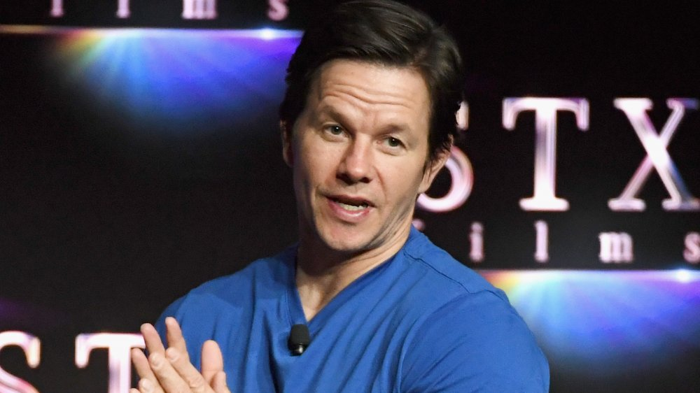 Mark Wahlberg in a blue shirt, speaking to a crowd