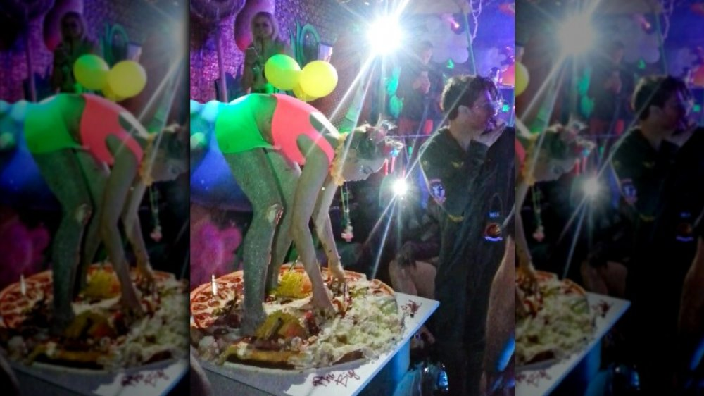 Miley Cyrus standing on her pizza cake at her 22nd birthday party