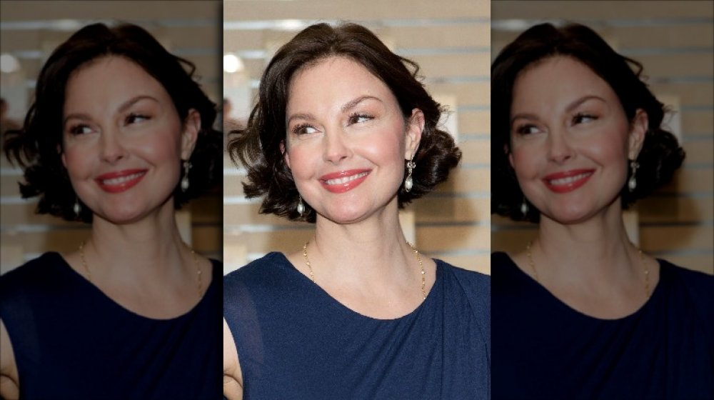Ashley Judd in a blue dress, smiling big while looking off to the side